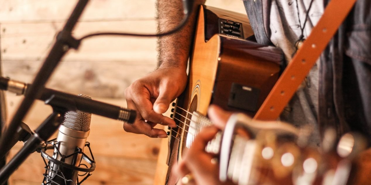person playing acoustic guitar 2291538 1 scaled e1595445129687